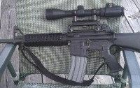 ar-15 with scope mounted high on fixed carry handle