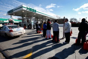 People stand in line with gas cans at a gas station on Staten Island in New York City after Hurricane Sandy
